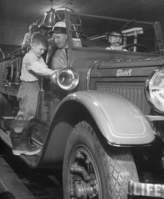 Young boys playing on their father's fire truck. Allentown, 1948.  ByNina Leen