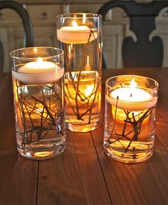 Simple glass vases with twigs and floating candles.