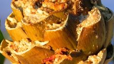 A stuffing made with Italian bread, garlic, parsley, Romano cheese and oregano is stuffed between the leaves of whole artichokes. The stuffed artichokes are then simmered slowly for an hour.