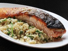 A quick and hearty meal of salmon cooked with quinoa, arugula, and feta cheese. The trick is to sear the salmon skin first, then add it back to the pan at the very end just until barely cooked through.