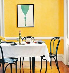 Yellow dining room with teal picture