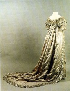 """While few dresses have survived the 200 years since the Regency Era, Princess Charlotte's silver wedding dress of 1816, still exists. Princess Charlotte of Wales, born Charlotte Augusta on 7 January 1796 – 6 November 1817, was the only child of Princess Caroline of Brunswick, and George, Prince of Wales who later became King George IV.The Museum of London recently exhibited this gorgeous creation. This elaborate gown in silver lace, called """"net"""" in those days, lays over white silk and cut in the"""