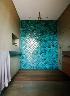 Modern bathroom with grey concrete floors and walls;  #turquoise fish scale #tiles in the walk-in #shower.