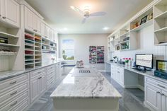 White melamine craft room with raised panel door and drawer fronts and crown molding. Multiple workstations and large island for crafting while standing.
