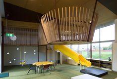 Mana Tamariki / Tennent + Brown, slide, play mezzanine, green flooring, plywood ceiling panels, plywood casework, wooden dowel railings