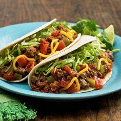 Tacos Especiales... Los tomates en cubos condimentados agregan un toque especial a los tacos duros rellenos de carne de res sazonada, lechuga y queso cheddar