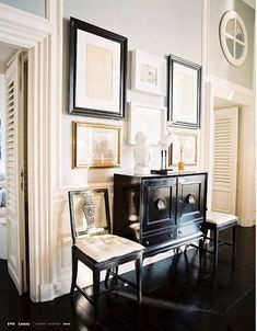 black chest with flanking chairs and art wall
