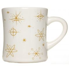 ATOMIC DINER COFFEE MUG WHITE WITH GOLD  Bring a little retro kitsch to your morning routine. This vintage reproduction coffee mug features an out of this world atomic starburst & star pattern in a muted gold color. Filler up & take sip, you'll feel like you're sittin' in your very own diner!  $8.00