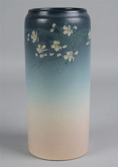 "ROOKWOOD ""VELLUM WARE"" ART NOUVEAU POTTERY VASE circa 1921, incised marks V and ETH for Edward T, Hurley, cylindrical and painted with apple blossoms against a shaded pink and blue ground - h:8 in. Other Notes: Edward T. Hurley (1869-1950)"