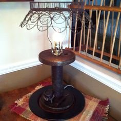 Lamp made from old spool and wire basket for shade.