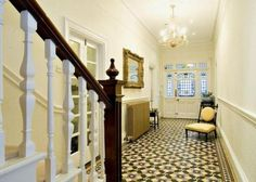 Victorian entry hall with original tiles and radiator. Olive green.