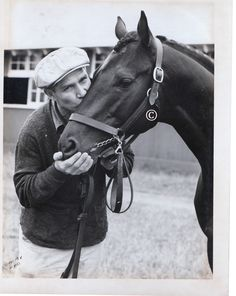 War Admiral, son of Man O'War gets a kiss from his groom.