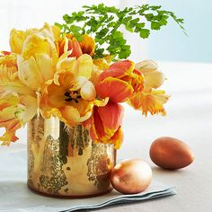 A shiny gold vase is the perfect home for bright yellow and orange flowers on your Easter table: http://www.bhg.com/holidays/easter/decorating/easter-table-setting-ideas/?socsrc=bhgpin041614ornateeastercenterpiece&page=8