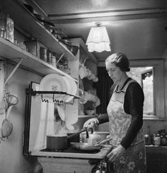 Mrs M Hasler cooks breakfast for her invalid husband at the stove in the kitchen of their home in Barnes. Great Britain, WW2