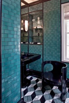 Powder room with turquoise tiled walls and black accents.