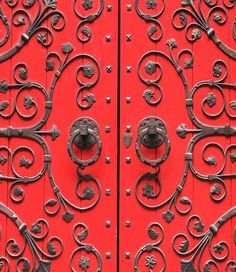 Red wood doors with ornate metal scrollwork.