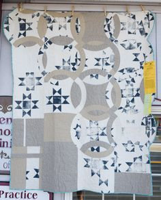 Christy Merritt describes her quilt, Ohio Wedding, as a mashup of two quilt challenges (Ohio Star Made Modern and Double Wedding Ring). She used a hand-carved linoleum block to print the Ohio stars, and used suiting fabric and curtains to construct the fragmented double wedding ring design.  2014 Sisters Outdoor Quilt show photo by Reanna Rosemarie Alder