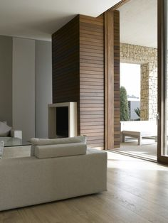 Modern rustic at it's best: Smooth, horizontal wood plan wall next to rustic, rough stone in a room with contemporary furniture.