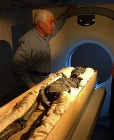 Dr. Zahi Hawass, Secretary General of the Egyptian Supreme Council of Antiquities, by Tut's mummy as it enters the CT scanner.