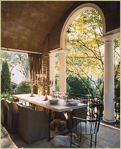 Classy covered patio. So well done. Every detail from the painted ceiling, columns and arch, iron railing, privacy curtains, to that beautiful tablescape. The doggies are pretty cute too :)