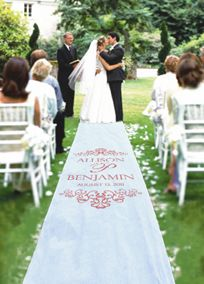 """Proudly display your names and wedding date to the world with this beautiful personalized fabric aisle runner. Aisle runner is a Victorian scroll print in white on white and is available only in pattern shown. Comes with a handy pull cord and instructions.  Features and Facts:  Personalized area is approximately 34"""" x 56"""" and is printed about 5-6 ft. from the front of the runner (where the alter would be).  Names, last name initial, wedding date and flourish design will appear in a watercol..."""