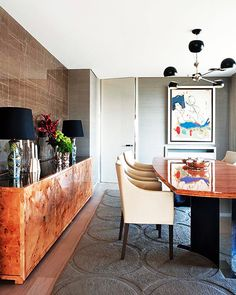 burl wood sideboard, marble wall, grass cloth wallpaper, black four-armed chandelier, circles rug, cream leather dining chairs // modern dining rooms