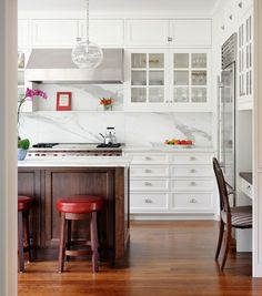 white kitchen cabinets, wood island and floors, pendants