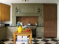 A New Colonial Kitchen - Old-House Online - Old-House Online   www.oldhouseonline.com-792 × 593-Search by image The stove niche is treated like a hearth. The yellow corner cabinet is also by Kevin Ritter; it hides the TV. The tall cabinet at right has a distressed, ...