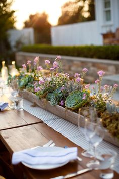 rustic planter with planted succulents, moss and flowers as centerpiece