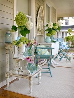Pretty simple really. The deck chairs are portable & inexpensive and the other furniture are older things painted white. The flowers are what bring it to life. I have a step table like this one in my sunroom that I use to put books, decorative watering cans, & whatever is blooming at the time. Good display piece.