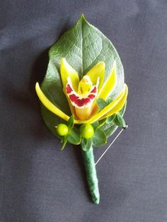 #boutonniere featuring green cymbidium orchid and green berries