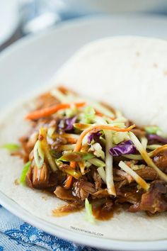 Slow cooker Korean tacos are so easy to make and the results are a tender, flavorful pork wrapped inside a warm tortilla and topped with a tangy slaw!
