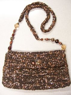 Look Amy - cassettes instead of VHS - makes a brown bag!!  Cassette Tape Beaded Bag ~ made with two strands of cassette tape & two strands of brown ribbon that came from a sweater. Magnetic button closure added with beads glued to cover the prongs on the outside. #reuse #repurpose #recycle #DIY #crochet #purse