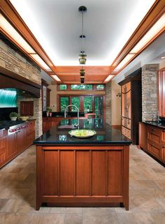 An Arts & Crafts style, Frank Lloyd Wright inspired kitchen with wood cabinets, stone floors and a glass backsplash.