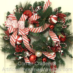 Christmas Candy Cane Wreath - 2013 - Candy canes surely are a holiday favorite for hanging on your tree, swirling in hot cocoas, or simply enjoying their wonderful peppermint flavor. Our Christmas Candy Cane Wreath is indoor and outdoor friendly. It has a multi-pine wreath base and is embellished with candy canes, shatterproof ornaments, and berries. The red and white striped bow complete the look. #ChristmasWreaths #ArtificialChristmasWreaths #CandyCaneWreaths #CandyCanes #Wreaths