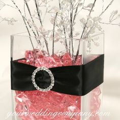 Wedding centerpiece using wide satin ribbon, a rhinestone buckle, and faux-pink ice.