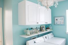 Bright blue laundry room with fun chandelier