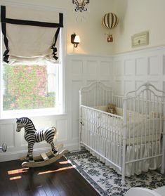 Love the look of a #black and #white #damask rug under a white crib in a classic #nursery.