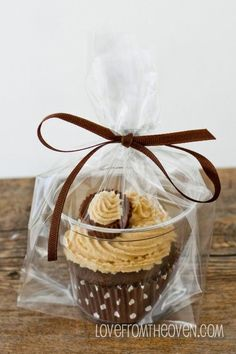 Perfect way to pack an individual cupcake: in a clear cup with a clear bag & tied with a ribbon. Brilliant!