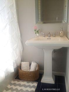Small chic bathroom with grey walls, pedestal sink and chevron rug  #smallbathroom #powderroom #idea #chevron #bathmat #bathroom #kohler #grey #pintuck #target #homegoods #homegoodshappy #sherwinwilliams #lightfrenchgrey #mirrored #mirror #showercurtain #basket #rustic #luxe #chic #mercuryglass #white