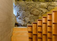 Pine staircase inside a concrete courtyard house positioned against a cliff.