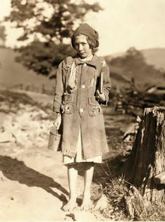 This picture shows a poor child, barefoot and wearing tattered clothes. It was taken in 1921 in Mlinton, West Virginia.