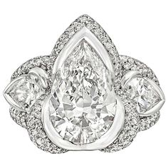 Mauboussin 3.05 Carat Pear-Shaped Diamond Ring. Diamond ring, centering on a colorless pear-shaped diamond weighing 3.05 carats, with pear-shaped diamond shoulders, the two diamonds weighing 1.02 total carats, the three larger diamonds each with fancy pavé-set diamond surrounds, mounted in 18k white gold, signed Mauboussin. Accompanied by GIA certificate for the pear-shaped diamond center. 21st century