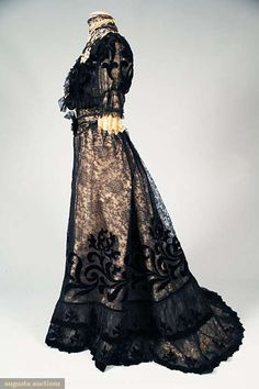 "BLACK LACE TEA GOWN, c. 1905  2 piece black Chantilly lace over ivory silk, lace appliqued w/ black velvet art nouveau designs, bodice front w/ cream lace appliques, shaped inset waist band, skirt slightly trained, double flounced hem, B 36"", W 22"", Skirt L 42""-48"", (silk bodice lining shattering, split at top front high neck, several holes in lace, esp. back bodice)"