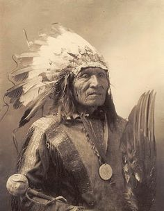 "A picture of a Sioux Indian Chief. The man's name is ""He Dog"". The picture was taken in 1900. He appears to be carrying some sort of large bird wing."
