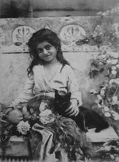 """A girl and a black cat (circa 1895). Photograph by Wilhelm von Gloeden (1856–1931) [From """"Sicilia mitica Arcadia. Von Gloeden e la """"Scuola"""" di Taormina"""" by Vincenzo Mirisola and Giuseppe Vanzella, Edizioni gente di fotografia, Palermo 2004, p. 26]"""