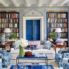 AnIksel Decorative Artswallpaper wraps the primary family room; the infanta painting is by Agustin Hurtado, and the chairs are slipcovered in Schumacher ikat ~ Miles Redd.