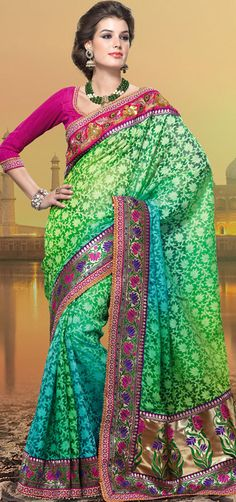 An occasion wear perfect is ready to rock you.   This shaded green and blue viscose saree is nicely designed with embroidered patch work is done with resham, zari, sequins, stone and lace work.   Beautiful embroidery work on saree make attractive to impress all.   This saree gives you a modern and different look in fabulous style.   Contrasting dark pink blouse is available.   Slight color variations are possible due to differing screen and photograph resolution.