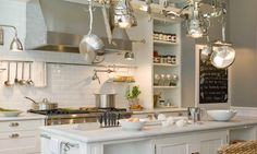 deulonder.com  ~Amazing kitchen with charcoal gray walls paint color, white kitchen cabinets & kitchen island, light gray quartz countertops, subway tiles backsplash, stainless steel pot rack & pot rack, pot filler, open shelves and chalkboard in kitchen.