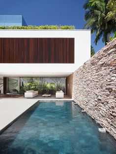 Pool with stone wall and tiled pool bottom. AH House by Studio Guilherme Torres